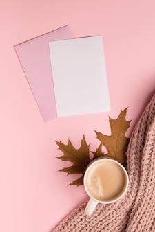 Gestileerde herfst achtergrond, kopje koffie, blanco papier en bladeren op roze tafel, flatlay.