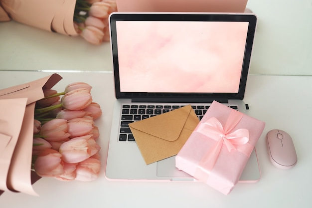 Gestileerde vrouwelijke bureauwerkruimte met roze tulpen, laptopcomputer en envelop. bovenaanzicht notebookscherm. roze geschenkdoos en roze computermuis.