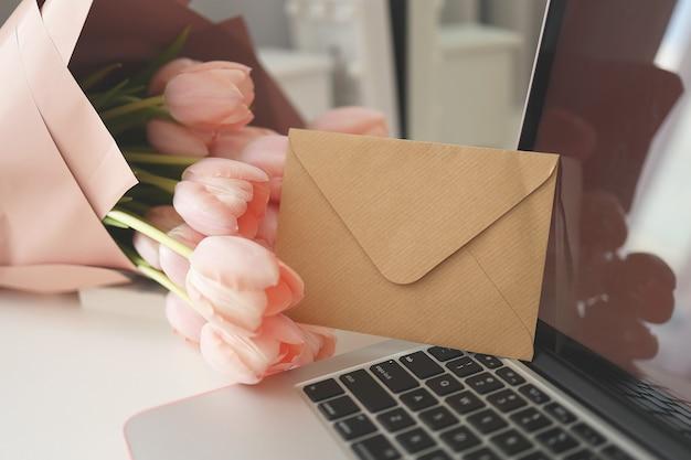 Gestileerde vrouwelijke bureauwerkruimte met roze tulpen, laptopcomputer en envelop.