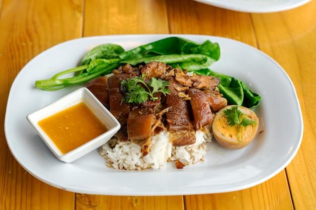 Gestoofd varkensvleesbeen op rijst met gekookt ei op houten lijst