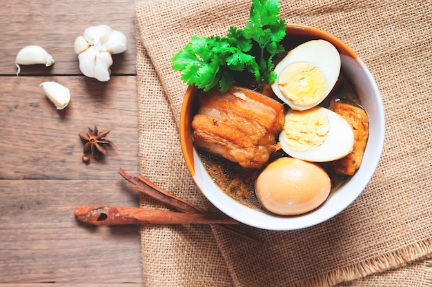 Gestoofde eieren en varkensvlees of eieren en varkensvlees in bruine saus in kom met kruiden op houten tafel