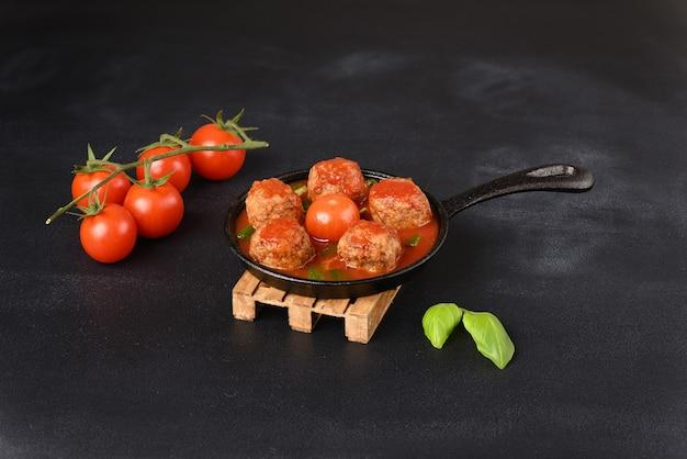 Gestoofde gehaktballetjes in tomatensaus in een pan op een donkere achtergrond