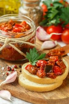 Gestoofde groenten (aubergine, paprika en tomaten) met knoflook, peterselie en kruiden op brood toast
