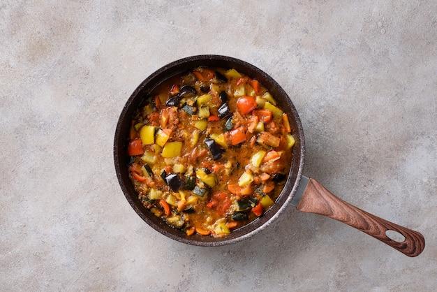 Gestoofde groenten in een pan: aubergine, tomaten, paprika, courgette, uien, olijfolie, kruiden. veganistisch gerecht.