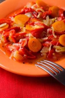 Gestoofde groenten op het oranje bord en het rode servet