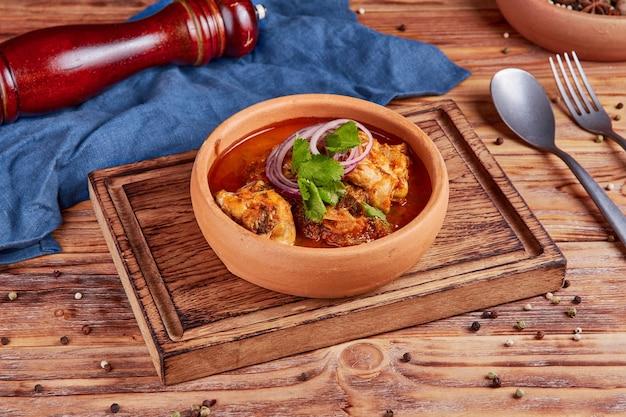 Gestoofde kip, tomaten, hete kruiden, georgische keuken, houten
