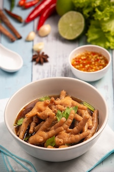Gestoofde kippenpootsoep geserveerd met pikante vissaus