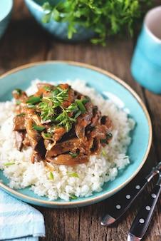 Gestoofde lever in een saus met ui, wortel en peterselie en gekookte rijst