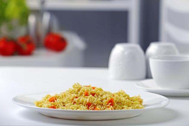 Gestoofde rijst met een wortel op een wit bord