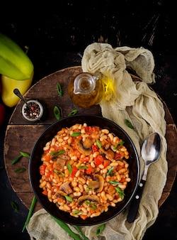 Gestoofde witte bonen met champignons en tomaten met pikante saus in een zwarte kom. . plat leggen