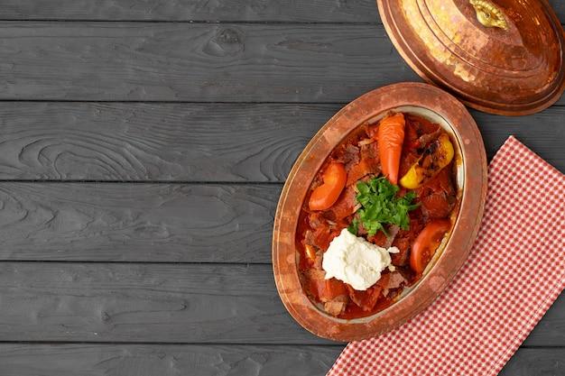 Gestoomd vlees met groenten in tomatensaus op houten