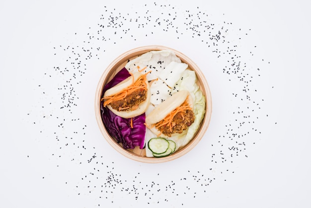 Gestoomde die broodjes in steamers met sesamzaden worden omringd op witte achtergrond