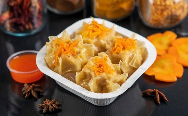 Gestoomde dim sum dumplings geserveerd met heerlijke saus