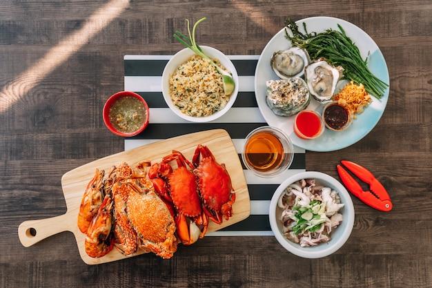 Gestoomde giant mud crabs en oosterse gerechten in houten snijplank