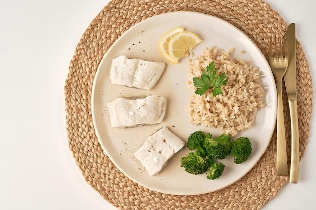 Gestoomde kabeljauw met bruine rijst en groenten, dash fodmap dieet bovenaanzicht