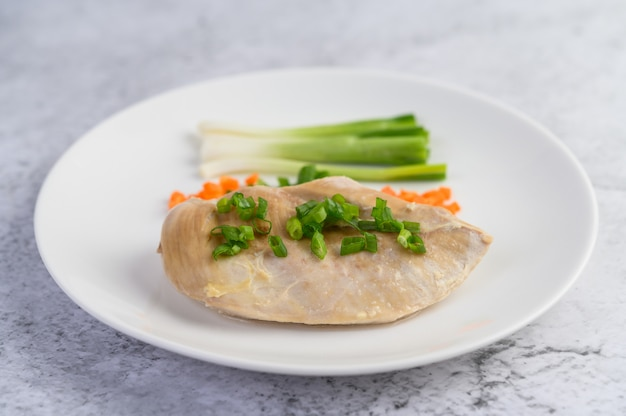 Gestoomde kipfilet op een witte plaat met lente-uitjes en gehakte wortelen