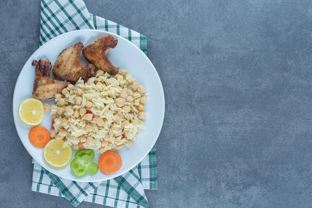Gestoomde rijst met kikkererwten en kippenvleugels op witte plaat.