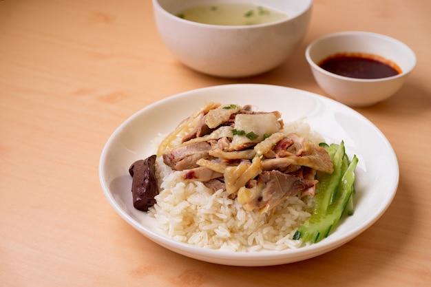 Gestoomde rijst met kippensoep op houten tafel