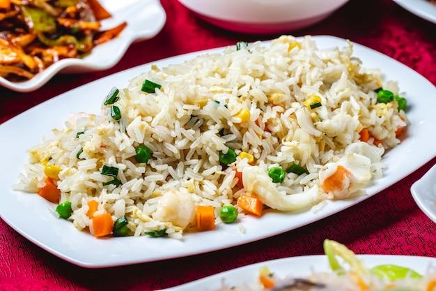 Gestoomde rijst met zeevruchten calamary corns wortel erwten zijaanzicht