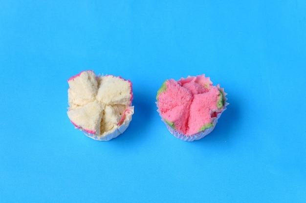 Gestoomde sponge cake, of bolu kukus-voedsel uit indonesië. geïsoleerd op een blauwe achtergrond