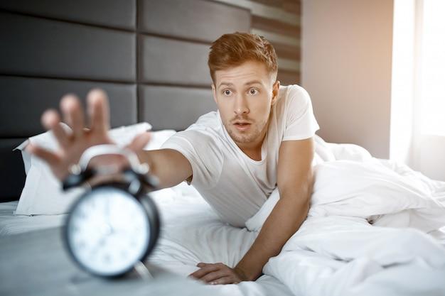 Gestoorde jonge man liggend op bed in de ochtend. hij heeft zich verslapen. guy bereiken klok met de hand.