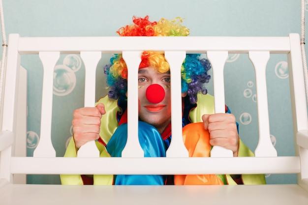 Gestrafte clown zit onder een bank.