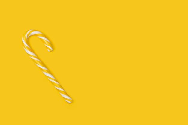Gestreept suikergoedriet op een gele achtergrond met exemplaarruimte