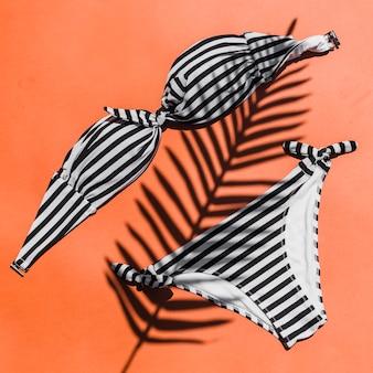 Gestreept vrouwelijk bikinizwempak op bladschaduw over de gekleurde achtergrond