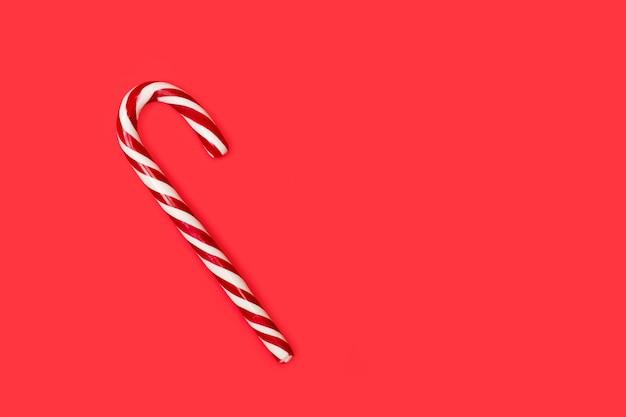 Gestreepte candy cane op een rode achtergrond met kopie ruimte