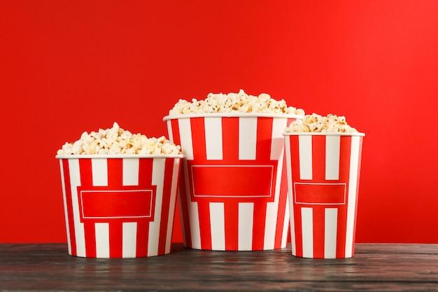 Gestreepte emmers met popcorn tegen rode achtergrond