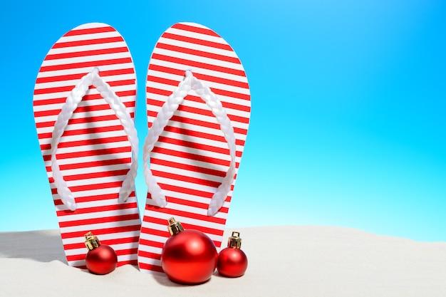Gestreepte flip-flops en kerst ornamenten op een tropisch strand staande op het zand tegen een zonnige blauwe hemel met kopie ruimte