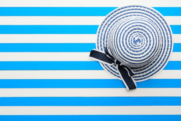 Gestreepte hoed op blauwe en witte achtergrond. bovenaanzicht, plat gelegd.