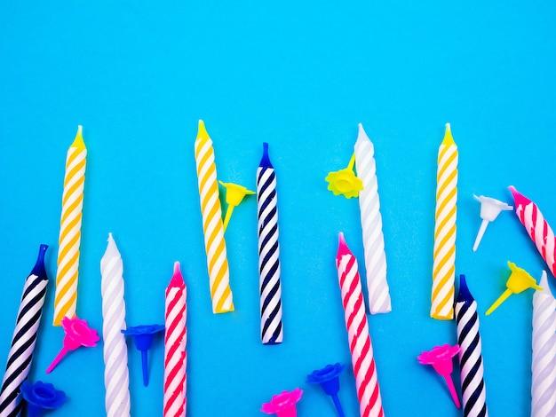 Gestreepte kleurrijke kaarsen voor verjaardagspartij op witte achtergrond. plat leggen.