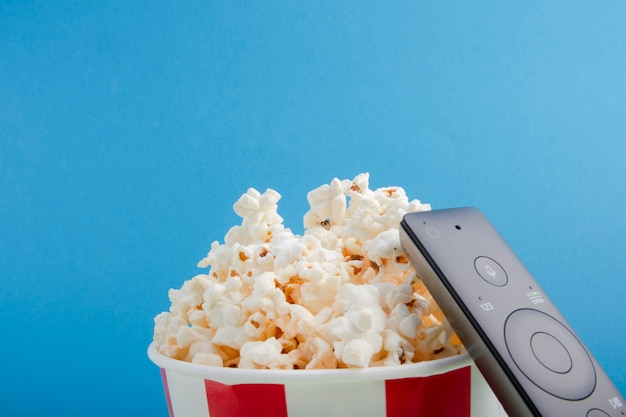 Gestreepte papieren beker met popcorn, afstandsbediening op tv