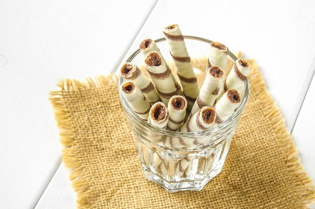 Gestreepte wafeltjebroodjes, heerlijke chocoladesnack op witte houten lijst.