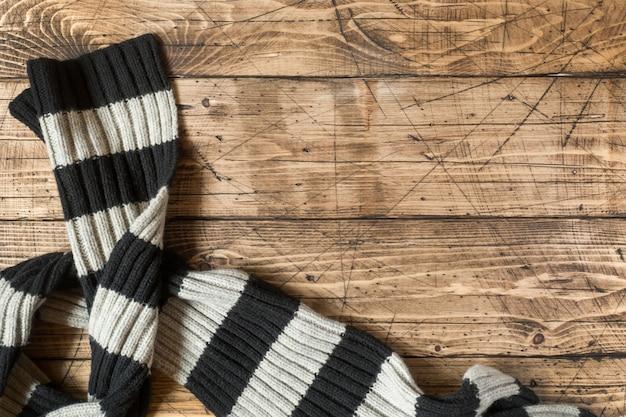 Gestreepte wollen sjaal op bruin houten oppervlak.