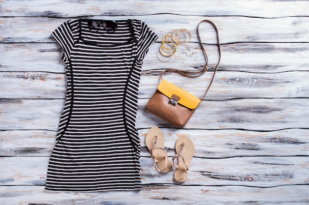 Gestreepte zwarte jurk en sandalen. beige sandalen met donkere jurk. casual zomeroutfit voor meisjes. hoge kwaliteit kleding op voorraad.