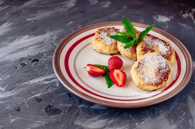 Gestremde melkpannenkoekjes met aardbeienmunt en poedersuiker in een witte plaat.