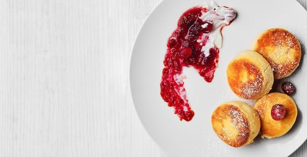 Gestremde pannenkoeken of kaaspannenkoekjes bestrooid met poedersuiker met room en cranberryjam