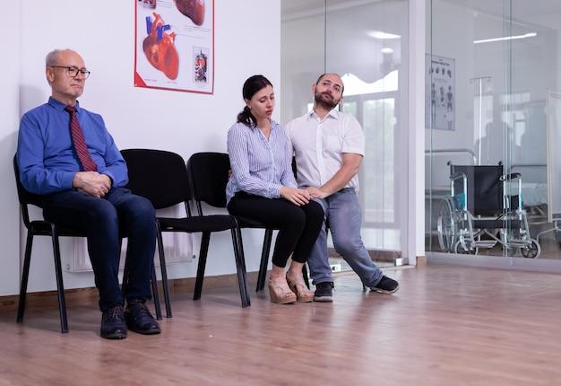 Gestresst getrouwd stel huilend in de wachtruimte van het ziekenhuis na slecht nieuws van de arts over de resultaten van de virustest. vrouw hoort ongunstig nieuws, terwijl senior man wacht om naar de onderzoekskamer te gaan.
