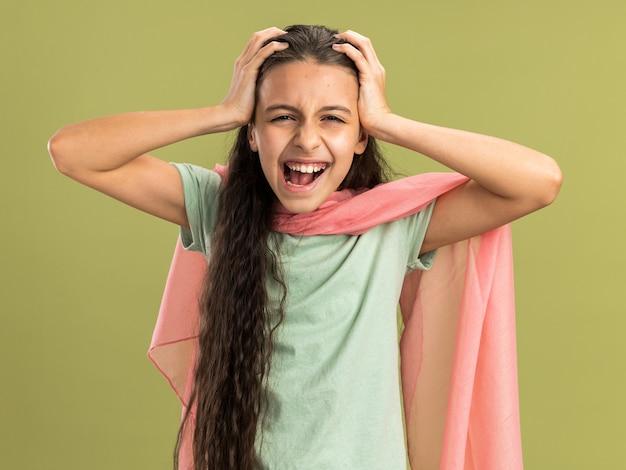 Gestresst tienermeisje met een sjaal die de handen op het hoofd houdt en naar de camera kijkt die op de olijfgroene muur is geïsoleerd