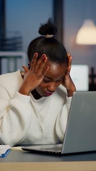 Gestresste afrikaanse zakenvrouw die lijdt aan hoofdpijn op het werk