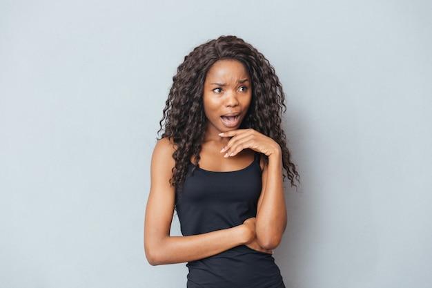Gestresste afrovrouw die op grijze muur schreeuwt