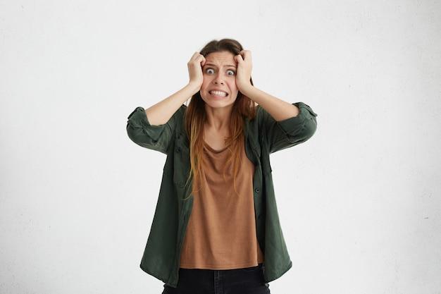 Gestresste, angstige jonge, nonchalant geklede vrouw die haar uittrekt, spanning en stress voelt terwijl ze met problemen wordt geconfronteerd, kan niet tegen druk, tanden op elkaar klemmen en de ogen openhouden.