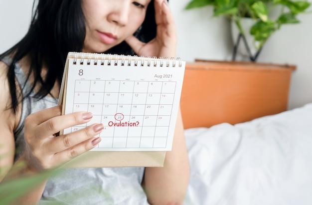 Gestresste aziatische vrouw met kalender die menstruatiecyclus controleert