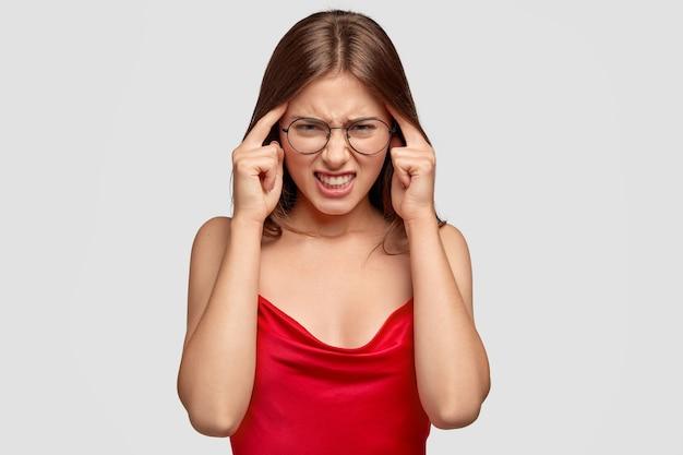 Gestresste brunette dame raakt tempels en denkt hard, heeft vreselijke hoofdpijn