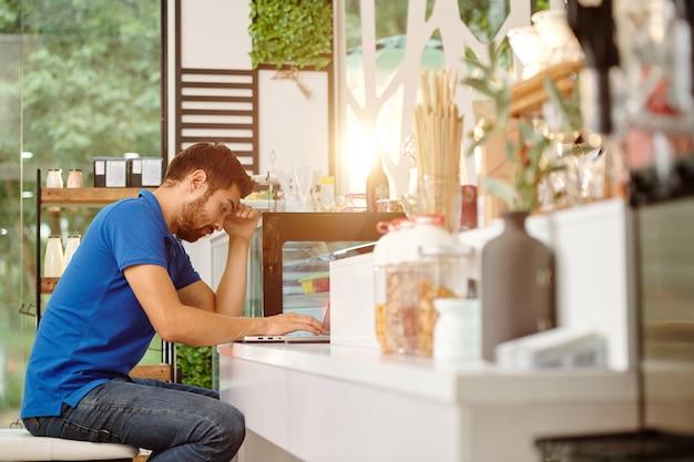Gestresste en vermoeide coffeeshopeigenaar die de kosten analyseert bij het werken op een laptop aan de balie