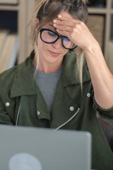 Gestresste en vermoeide volwassen vrouw aan het werk thuis met online laptopcomputer in slim werkend modern