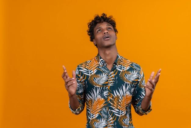 Gestresste en verwarde jonge knappe donkerhuidige man met krullend haar in bladeren bedrukt overhemd dat zijn handen op een oranje achtergrond opheft