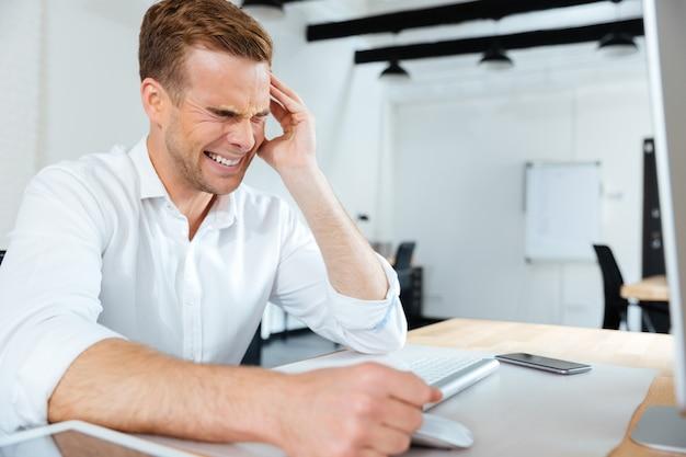Gestresste gespannen jonge zakenman die lijdt aan hoofdpijn op kantoor